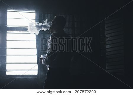 Pensive looking businessman relaxing after work closeup. Man leisure with alcohol and smoking in private club, bad habits. Dark atmospheric place with free space