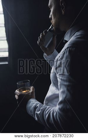 Thoughtful looking male relaxing after work. Man leisure with alcohol and vape in private club, bad habits. Luxury life with whiskey and smoking, dark place background