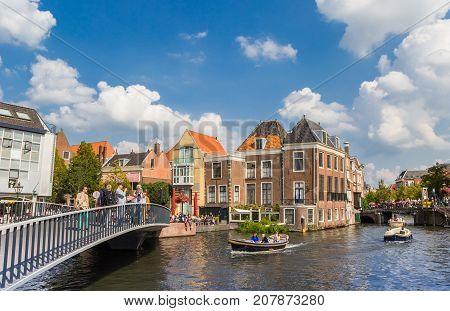 LEIDEN, NETHERLANDS - SEPTEMBER 03, 2017: Small boats passing under bridges in the center of Leiden Holland