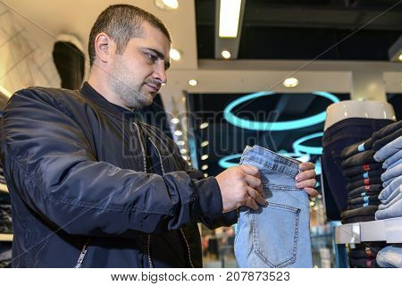 young man with short hair chooses jeans with a good mood