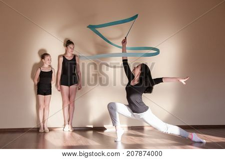 Rhythmic gymnastics. Ballet master class. Ballerinas lessons education, teenage sport, healthy teen lifestyle. Female coach with young girls, brown wall background