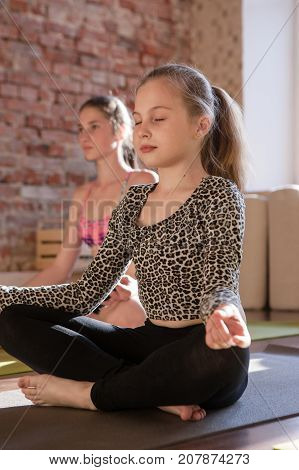 Zen life for child. Self-improvement. Young meditating girl in yoga studio, teenage sport in focus on foreground. Gym background, healthy lifestyle, thoughts concentration