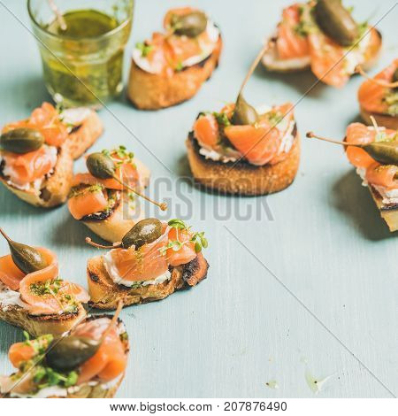 Crostini with smocked salmon, pesto sauce, watercress and capers over light blue background, selective focus, copy space, square crop. Party, catering or fingerfood concept