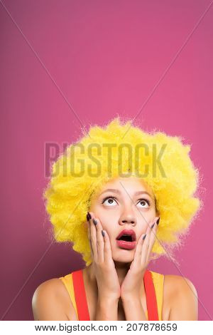 a funny girl in a bright yellow wig is very frightened and looked up