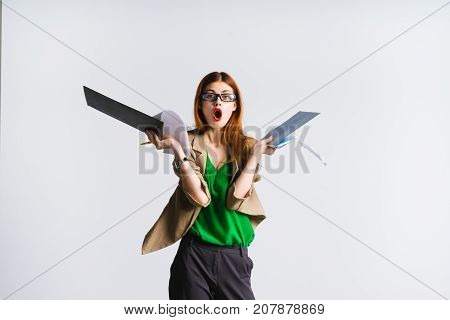 a surprised and frightened girl with red lips holds some papers in her hands and looks into the camera