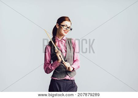 funny teacher with glasses with a pointer in her hand looks directly at the camera, isolated