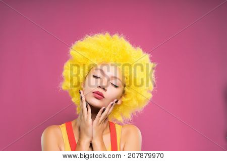 funny girl in a yellow wig closed her eyes, isolated on a pink background