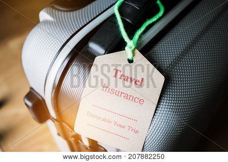 Travel Insurance tag on Suitcase safety with letters enjoyable your trip on bag light blurred background that is intended cover medical expenses trip cancellation or flight accident.
