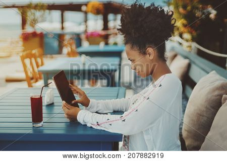Charming young African American girl with curly hair using digital tablet while sitting on the bench with cushions behind her back and waiting food order in street restaurant nearshore on a sunny day