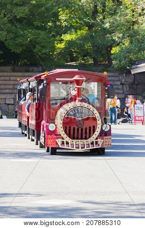 OSAKA JAPAN - SEPTEMBER 18 : unidentified asian sitting in the red road train shuttle car to bring the tourist go to Osaka castle on September 18 2017 in Osaka Japan.