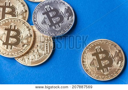 Several Coins Of Bitcoins On A Blue Background With One Gold And Bitcoins Coins Falling Out Of Their