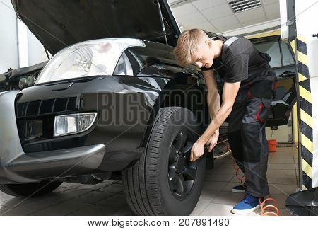 Young mechanic working in body shop
