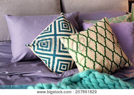 Lilac accent in modern interior. Pillows and plaid on comfortable bed at home