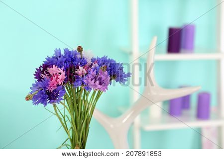 Lilac accent in modern interior. Beautiful bouquet of cornflowers in living room
