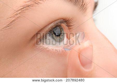 Young woman putting contact lens, closeup