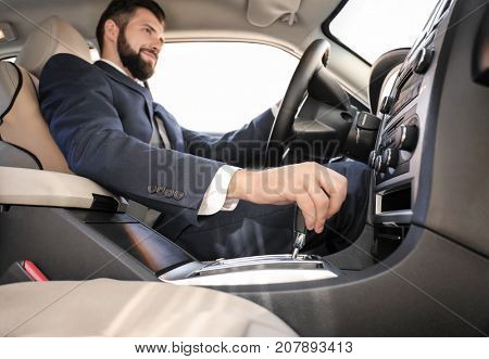 Handsome man in formal suit on driver's seat of car