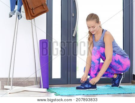 Young sporty woman tying shoelaces near door at home