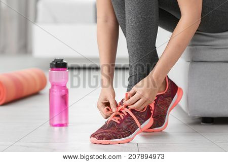 Young sporty woman tying shoelaces at home
