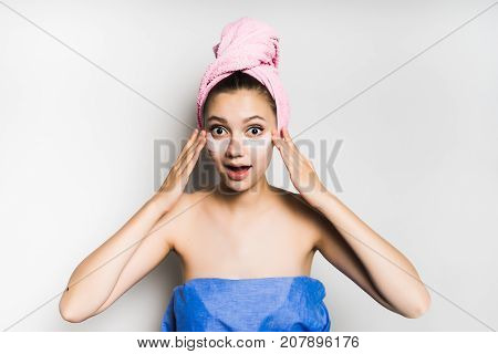 girl with towel on her head after shower puts on face under eyes patches