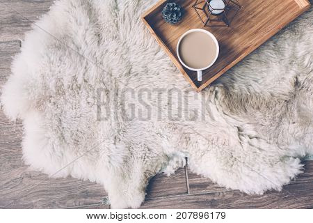 Mug with coffee and home decor on wooden serving tray on sheep skin rug. Winter weekend concept, top view