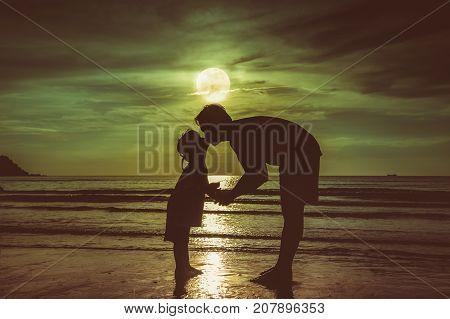 Father's Day. Silhouette Side View Of Loving Child Kissing Her Father.