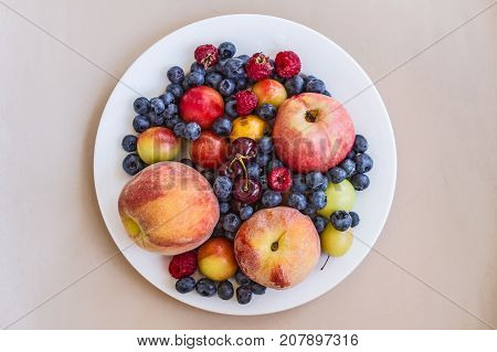 A plate of appetizing ripe juicy sweet fruit and berries: peaches, apples, plums, cherry plums, raspberries, blueberries, cherries on a creamy background.