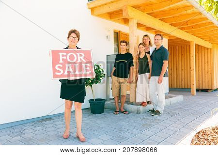realtor with family selling their house, standing in front of building