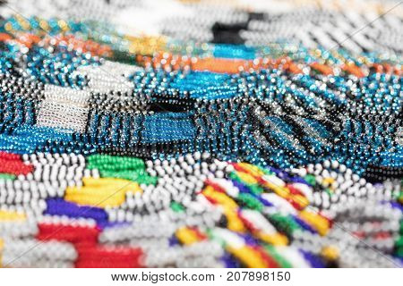 Glass bead necklaces for sale in an African market. These traditional tribal beads are sold all over Africa as souvenirs.  Intentional shallow depth of field.