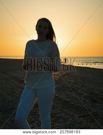 Beautiful woman in white clothes enjoying the sunset on the beach. Portrait of a beautiful woman by the sea.