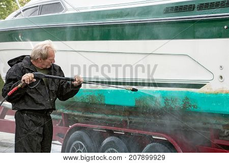 Caucasian man cleaning dirty boat hull with pressure washer