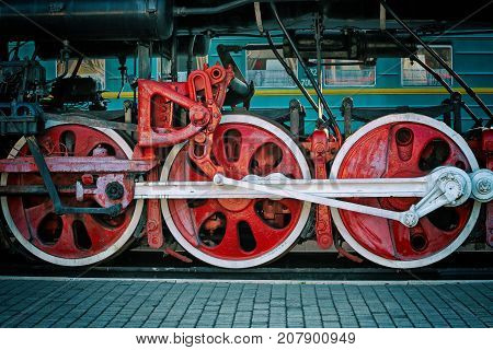 Retro steam  locomotive wheels and rods closeup. Details of mechanical parts, wheels and equipment of the train. Steam-punk style background