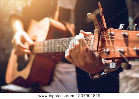 Asian hipster man left hand catch chord and playing music.