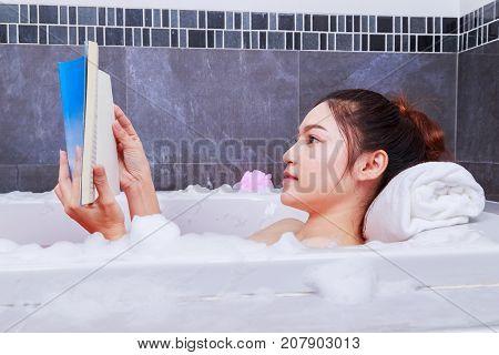 Woman Reading Book In Bathtub In Bathroom