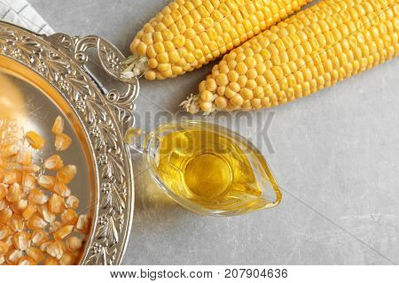 Glass gravy boat with corn oil on grey background