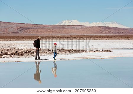 family of two father and son hiking and walking together enjoying salty lagunas escondidas in atacama desert chile healthy active family lifestyle and vacation concept