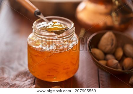 Peach jam in a transparent jar on the dark table