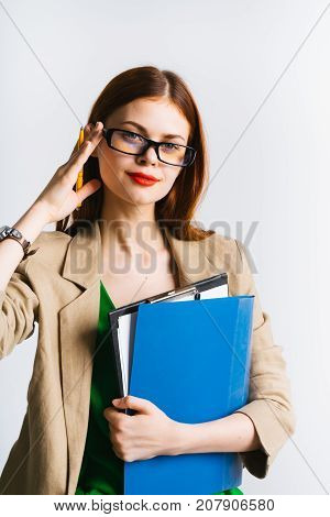 smart red-haired girl with glasses is holding documents and a pencil in her hands, looking away