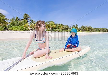 positive smiling boy in rashguard and his young mother enjoying stand up paddleboarding active healthy family vacation concept wide angle shot