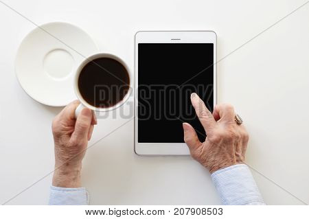 Close up shot of wrinkled hands of retired woman holding cup of black coffee and using touchpad with copy space screen working online or surfing internet sitting at white desk at home office