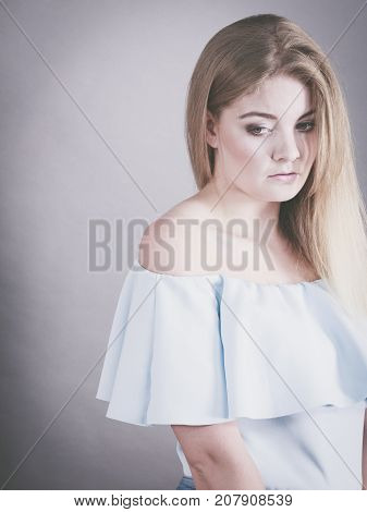Sad depressed young blonde woman having bad mood feeling distraught. Gray background