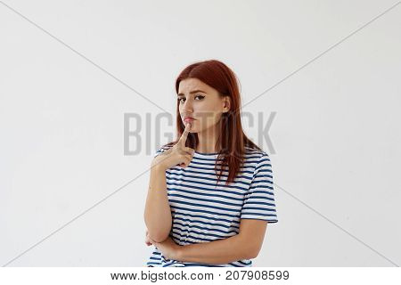 Let me think. Pensive uncertain young Caucasian female keeping finger on her chin and looking at camera with indecisive unsure expression feeling hesitant about what to wear for a walk or date