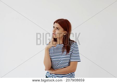 Attractive thoughtful young female planning summer vacations having doubtful pensive look holding hand at her face and looking up having deep in thoughts facial expression. Body language