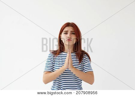 Pretty teenage girl pleading begging parents to let her go out with friends to night club keeping hands pressed together. Sad mournful young woman praying standing against studio wall background