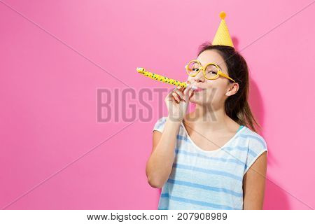 Happy woman celebrating with a party hat on a pink background