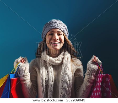 Happy young woman holding shopping bags on a dark blue background