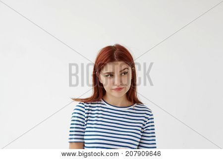 Pictures of beautiful young female with red hair pursuing lips and looking sideways with suspicion on her face raising eyebrow. Suspicious woman feeling distrust toward her unfaithful boyfriend