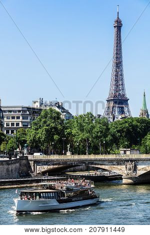Paris France - July 07 2017: Tourists watch the sights of Paris from the River Seine by a cruise tourist ship. The Invalides Bridge (Pont des Invalides) and the Eiffel Tower in the background.