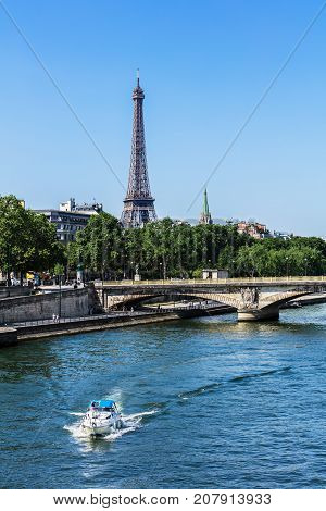 Paris France - July 07 2017: View of the River Seine with cruise tour boat the Invalides Bridge (Pont des Invalides) and the Eiffel Tower.