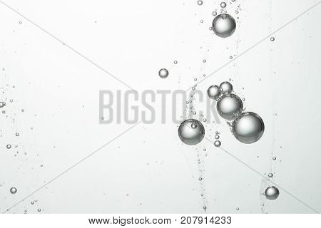 Flowing water bubbles over a white blurred background.