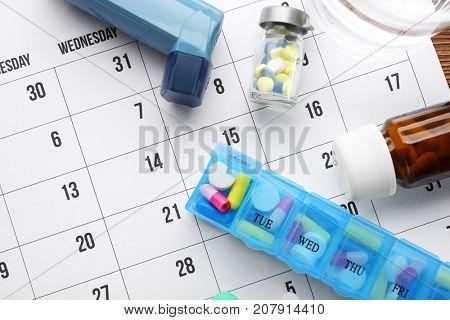Asthma inhaler and different pills on paper calendar
